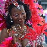 Woman in red smoking a cigar at the Notting Hill Gate Carnival