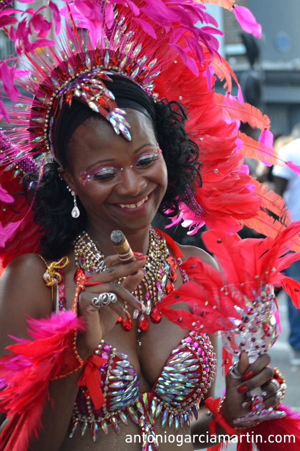 Woman in red smoking a cigar at the Notting Hill Carnival