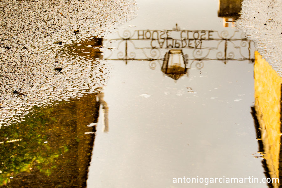 The Candem Close House sign reflection in a puddle